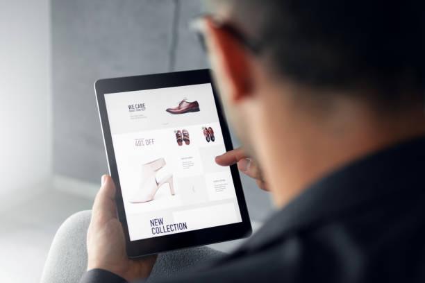 Homme qui regarde un site de chaussures en ligne sur une tablette numérique