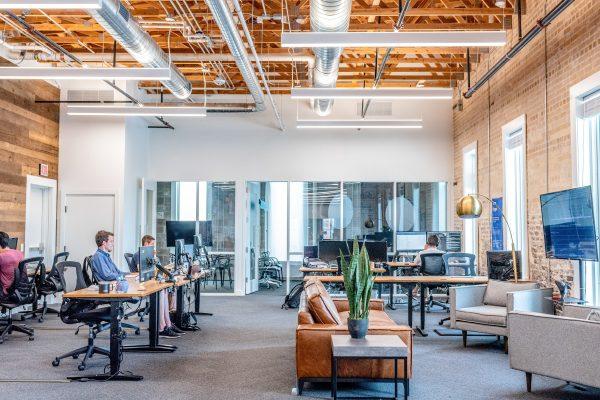 Grande pièce au style industriel dans laquelle sont installés les bureaux d'une entreprise
