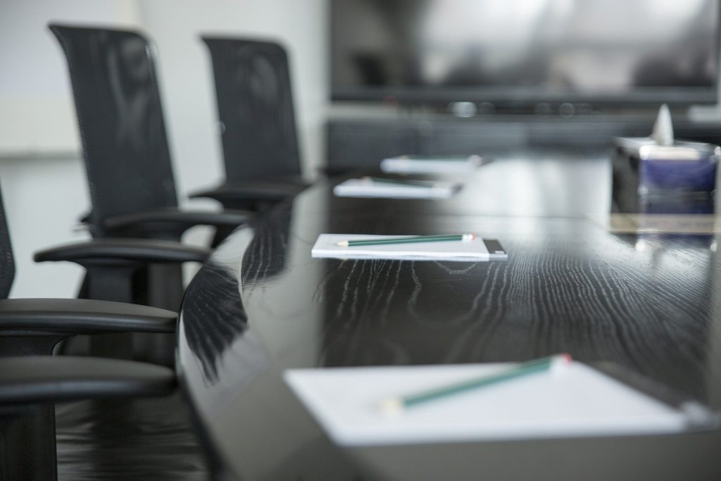 Salle de réunion avec une table au centre sur laquelle sont posés des carnets avec stylos à chaque place et des chaises de bureau autour