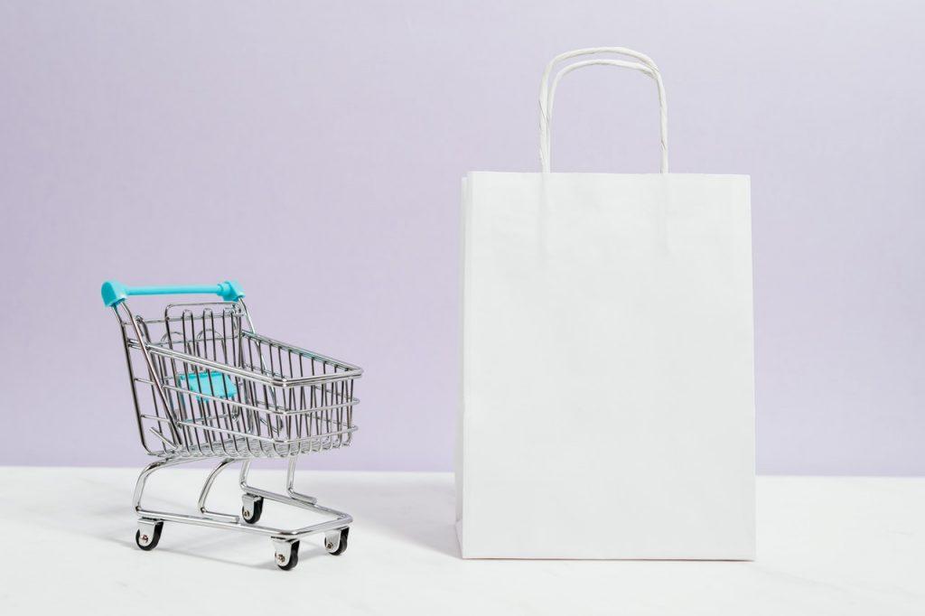caddie miniature à côté d'un sac en papier blanc